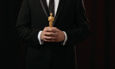 cropped-view-of-man-in-suit-holding-oscar-award-on-dark-background