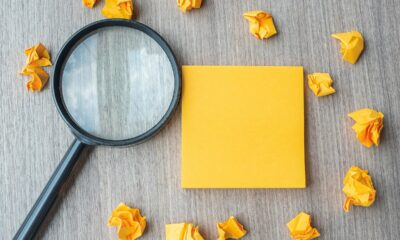 empty-yellow-note-with-crumbled-paper-and-magnifying-glass-on-wo