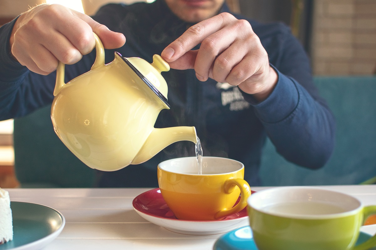mans-hand-with-a-yellow-teapot-pours-herbal-tea-into-a-cup-tea